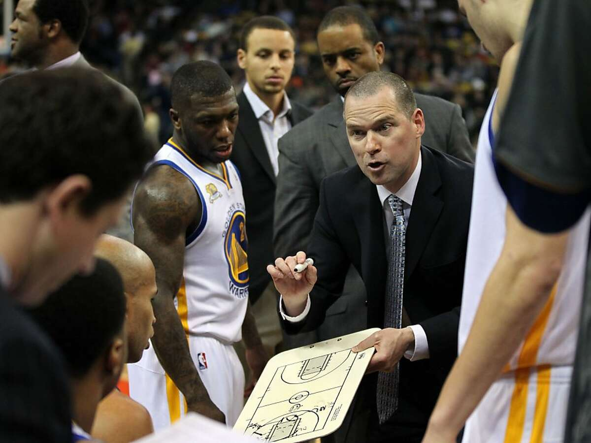 Golden State Warriors' assistant coach Michael Malone, right, talks with his players after drawing up a play during a timeout in the second half of their NBA basketball game with the Dallas Mavericks Thursday, April 12, 2012, in Oakland, Calif.