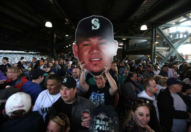 A fan carries an image of pitcher Felix Hernandez on the main concourse during the Seattle Mariners' home opener against the Oa