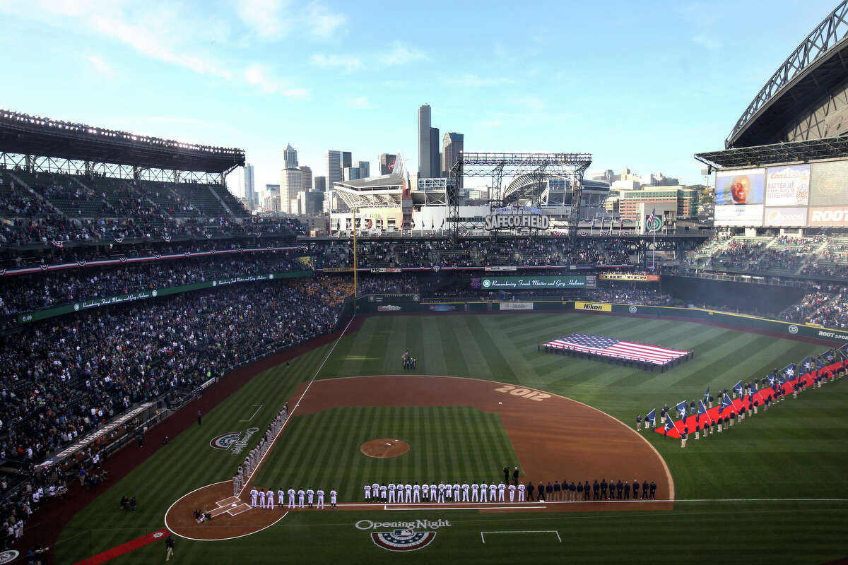 The Mariners and Athletics stand on the baseline during pre-game introductions.