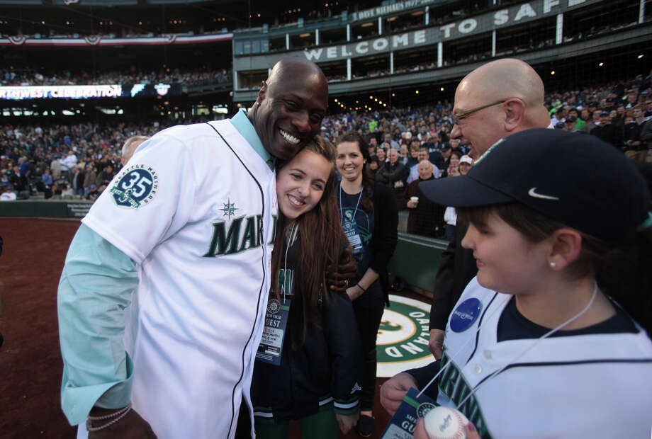 Newly retired Mariner Mike Cameron hugs Amanda Hanstad, 17, after Cameron threw out the ceremonial first pitch. Hanstad's sister did the ceremonial running of the bases. Photo: JOSHUA TRUJILLO / SEATTLEPI.COM