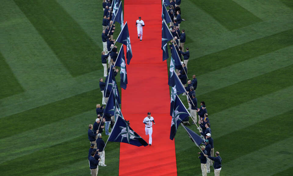 Mariners players run down a red carpet during introductions.