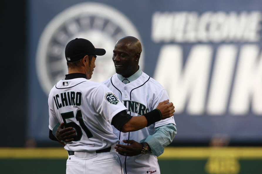 Mike Cameron embraces former teammate Ichiro Suzuki as Cameron throws out the ceremonial first pitch