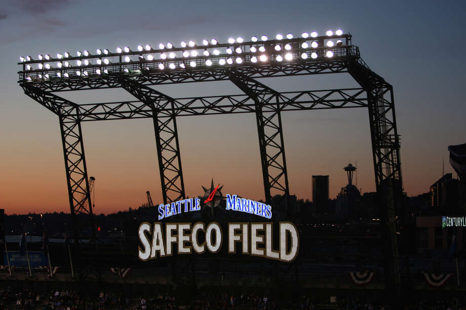 The Safeco Field sign is illuminated against the sunset during the Seattle Mariners home opener. Photo: JOSHUA TRUJILLO / SEATTLEPI.COM