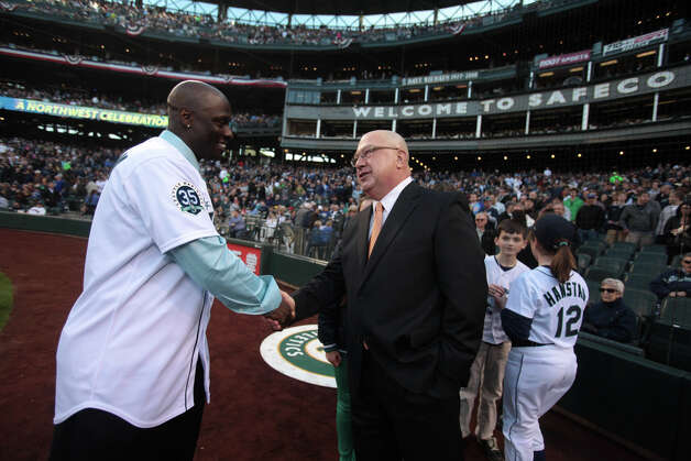 Former Mariner Mike Cameron shakes hands with Mariners General Manager Jack Zduriencik after Cameron threw out the ceremonial first pitch. Photo: JOSHUA TRUJILLO / SEATTLEPI.COM
