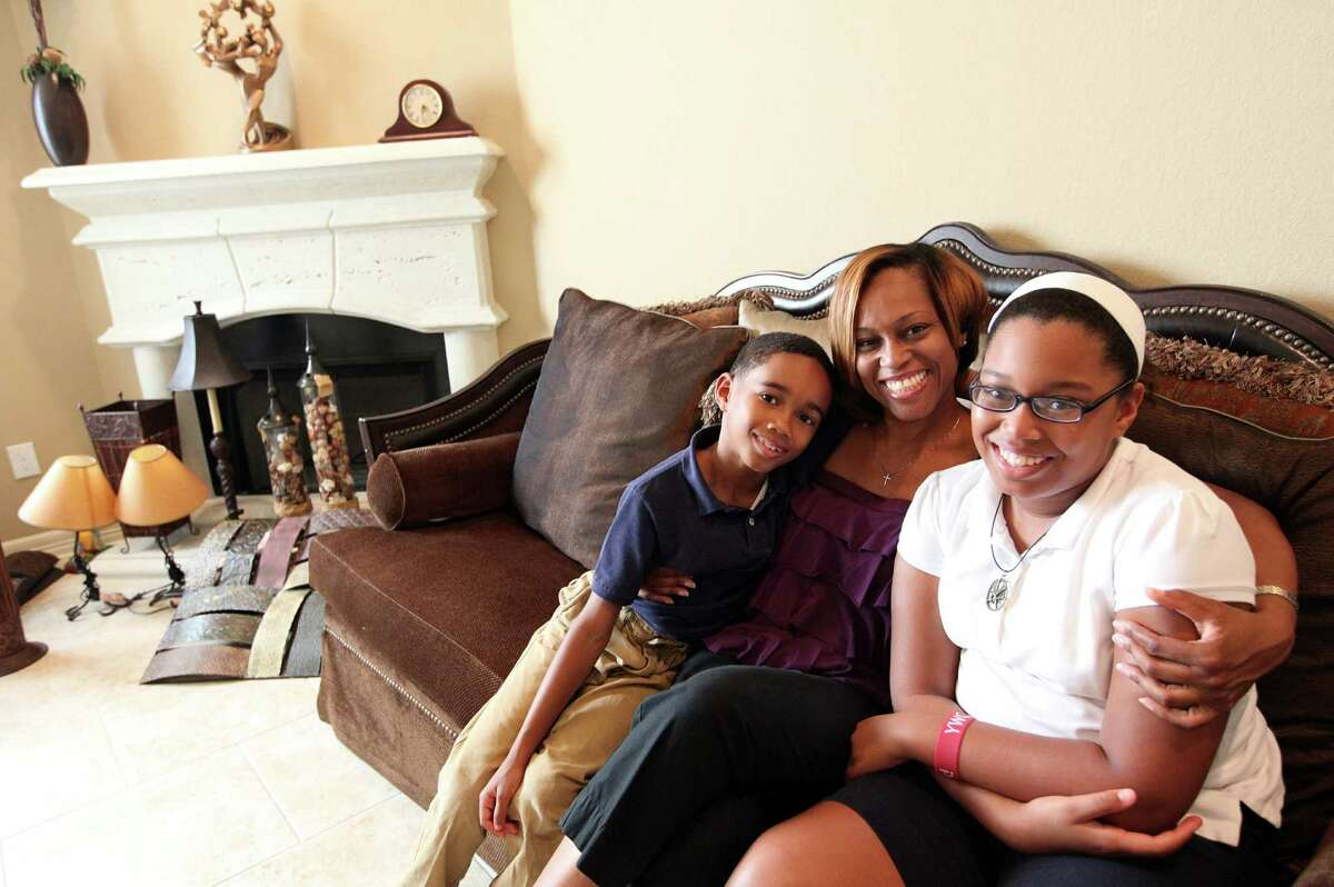 Kimberly McCann embraces son Carson Smith, 8, and daughter Kennedy Smith, 11, in their living room where they just moved into their new house near Texas Southern University on Tuesday, April 10, 2012, in Houston. McCann bought this house from the builder before it was even complete, and this is an example of how homes inside the Loop are out performing the rest of the market. ( Mayra Beltran / Houston Chronicle )