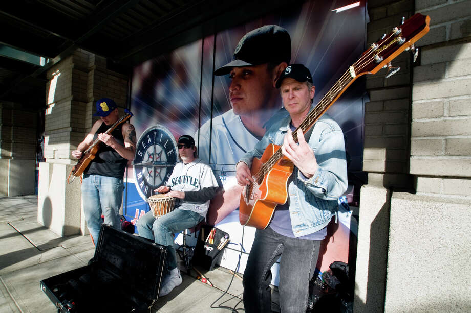From left, friends Kaare Kent, Mitch Anderson and Mark Brydahl play  their first gig as a band next to a photo of pitcher Jason Vargas  outside Safeco Field. Photo: LINDSEY WASSON / SEATTLEPI.COM