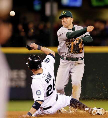 Oakland shortstop Cliff Pennington, right, throws to first after forcing out Seattle's Brendan Ryan at second in the eighth inning. Chone Figgins was out at first on the double play. Photo: AP