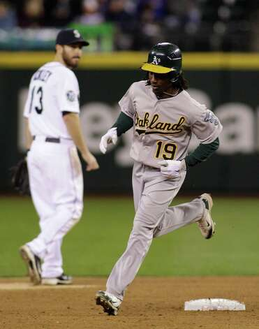 Oakland's Jemile Weeks (19) rounds the bases as Seattle's Dustin Ackley looks on at left, after Weeks hit a solo home run in the ninth inning. The A's beat the Mariners, 4-0. Photo: AP