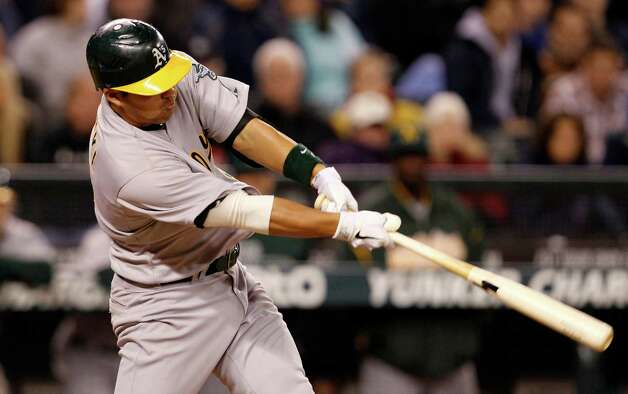 Oakland's Kurt Suzuki hits a sacrifice fly to score Josh Reddick in the eighth inning. Photo: AP