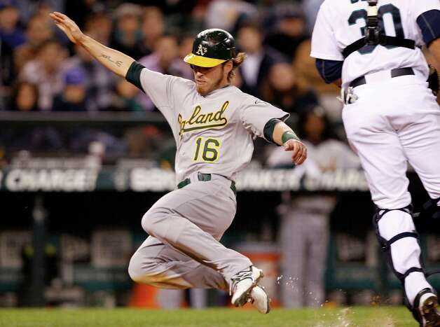Oakland's Josh Reddick (16) scores on a sacrifice fly by Kurt Suzuki as Mariners catcher Miguel Olivo waits for the ball in the eighth inning. Photo: AP