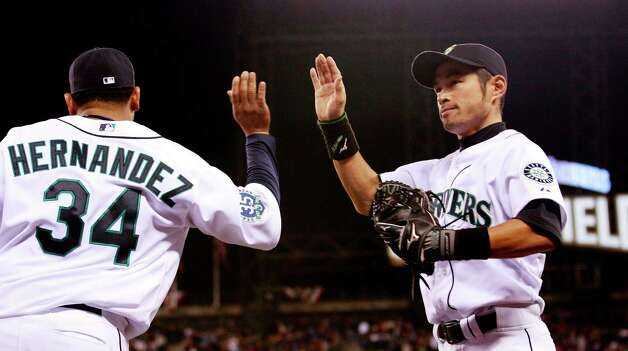 Mariners starting pitcher Felix Hernandez (34) high-fives right fielder Ichiro Suzuki after Suzuki caught a deep fly ball from Oakland's Coco Crisp in the seventh inning. Photo: AP