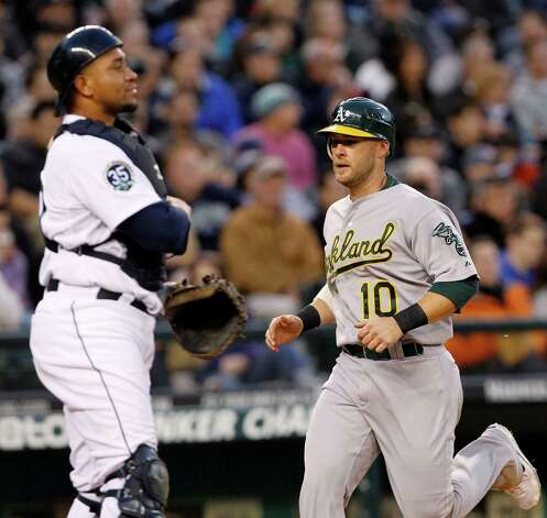 Mariners catcher Miguel Olivo watches as Oakland's Daric Barton scores on a double by Cliff Pennington in the third inning. Photo: AP