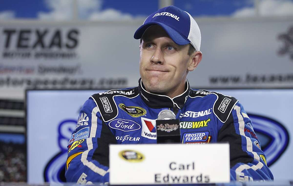 Carl Edwards listens to a question about his former girlfriend Olympic gold medal winning swimmer Amanda Beard's book during an availability at Texas Motor Speedway, Friday, April 13, 2012, in Fort Worth, Texas. (AP Photo/Tim Sharp)