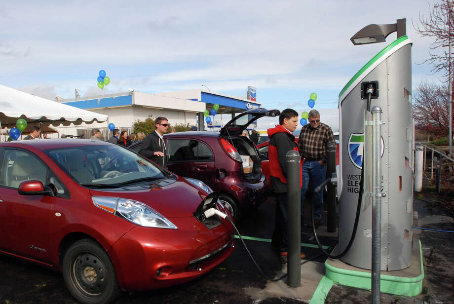A Nissan Leaf driver tops off the electric vehicle's battery in Central Point, Ore.,  at one of the charging stations along Interstate 5. U.S. car buyers bought a record number of hybrid and electric cars in March, as new models went on sale and gasoline prices neared $4 per gallon. Photo: JEFF BARNRD / AP2012
