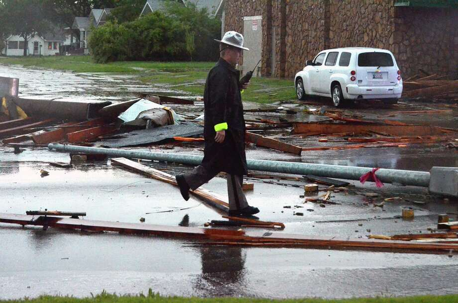An Oklahoma Highway Patrol office walks along Porter Avenue inspecting damage that was done to the area by a tornado that hit  Friday afternoon April 13, 2013 in Norman, Okla. Photo: The Norman Transcript, Kyle Phillips