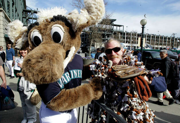 """Moose,"" the Seattle Mariners' mascot, greets George ""The Moose Man"" King outside Safeco Field prior to the Mariners' home opener MLB baseball game against the Oakland Athletics, Friday, April 13, 2012, in Seattle. King keeps track of the Mariners victories he has seen in person at Safeco by wearing hundreds of miniature Mariner Moose stuffed animals all over his body. Photo: Ted S. Warren / Associated Press"