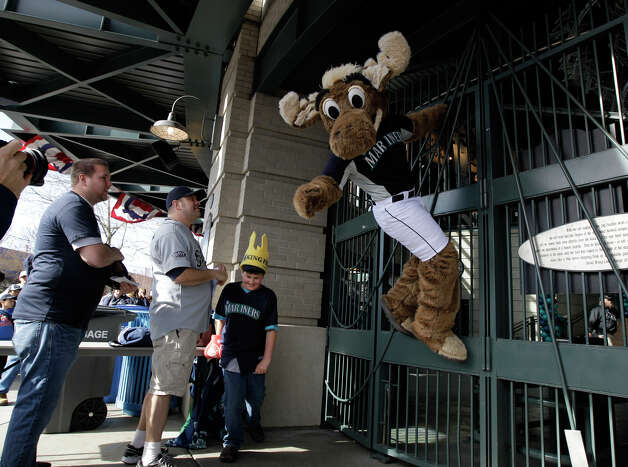 "Fans look on as ""Moose"" the Seattle Mariners' mascot, climbs the locked gates of Safeco Field as he waits to get in for the Mariners Home Opener against the Oakland Athletics in a baseball game on Friday, April 13, 2012, in Seattle. Photo: Ted S. Warren / Associated Press"