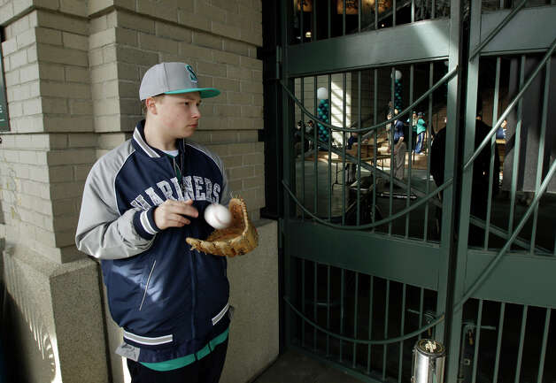 J.J. Keller, 16, of Bothell, Wash., tosses his baseball into his mitt as he waits for the gates of Safeco Field to open for the Mariners Home Opener against the Oakland Athletics in a baseball game on Friday, April 13, 2012, in Seattle. Keller said this is the fourth opening day in-a-row he has attended, and he got in line more than two hours early to claim his first-in-line spot Friday. Photo: Ted S. Warren / Associated Press