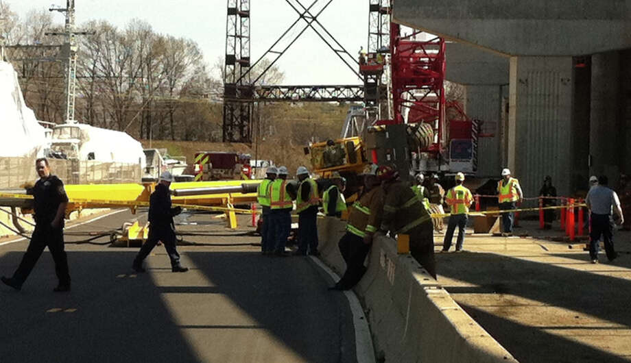 A crane used in the construction of the Moses Wheeler Bridge collapsed shortly before 9 a.m. today.  Police said the crane's boom toppled onto a metal building and struck an electrical panel near a work staging area near the Dock Shopping Center. Police said it is unknown how serious the operator of the crane was injured. Photo: Autumn Driscoll / Connecticut Post