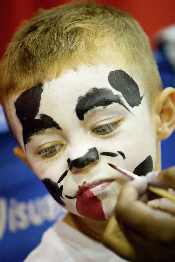 Dash Perez, 3, of Corpus Christi,  gets his face painted like a Dalmatian as he visits the Houston PetEXPO. Photo: Nick De La Torre, Houston Chronicle / © 2012  Houston Chronicle