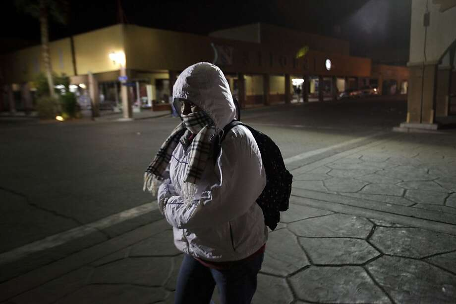 ADVANCE FOR USE MONDAY, APRIL 2, 2012 AND THEREAFTER - In this March 7, 2012 photo, Maria Guadalupe Pimentel walks along the dark streets of Calexico, Calif. before dawn on her way to the lettuce fields of the Imperial Valley. Thousands of Mexicans leave their homes each morning to become a pillar of one of most unusual and depressed labor markets in the United States. California's Imperial Valley consistently registers the nation's highest unemployment rate - 26.4 percent in January - yet it looks south of the border to fill many of its jobs because locals shun $9-an-hour jobs picking crops. Mexicans enter the country legally each morning and return home each night. (AP Photo/Gregory Bull) Photo: Gregory Bull, Associated Press