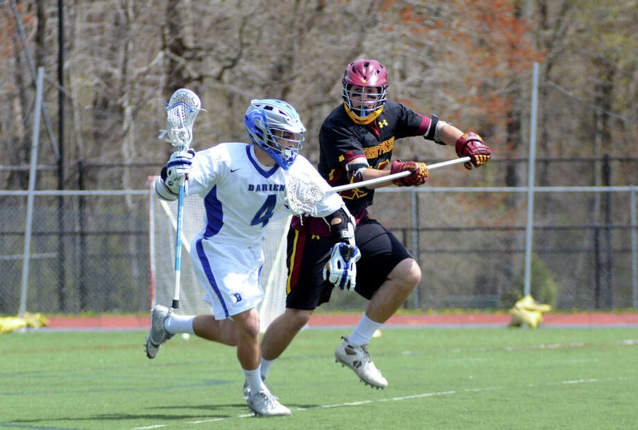 Darien's Case Matheis (4) controls the ball as Torrey Pines California's Christopher Carter (16) defends during the East meets West lacrosse invitational at Darien High School on Saturday, Apr. 14, 2012. Photo: Amy Mortensen / Stamford Advocate Freelance