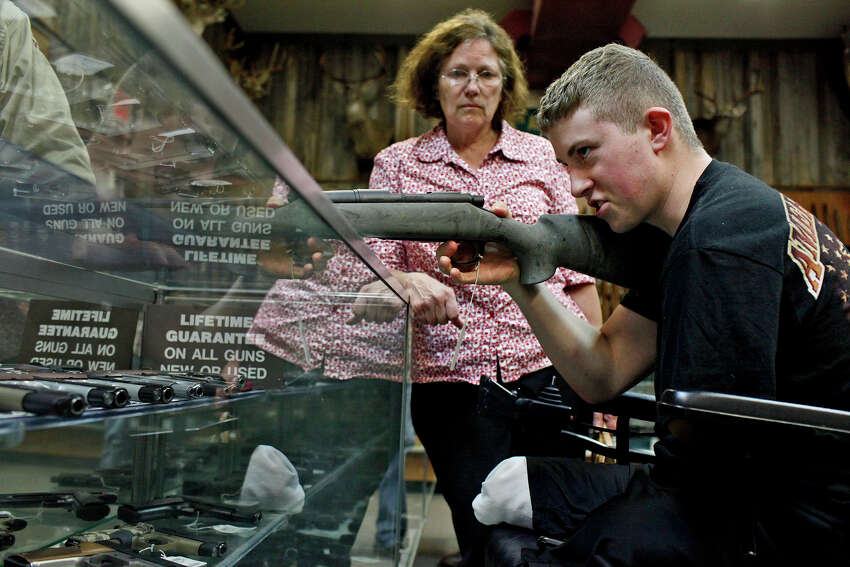 Saralee Trimble watches as her son, Army Pfc. Kevin Trimble, 19, shops for a hunting rifle at Dury's Gun Shop in San Antonio on Wednesday, March 7, 2012. Trimble was looking to buy his own rifle, since he's been borrowing one, for hunting trips with wounded warriors.