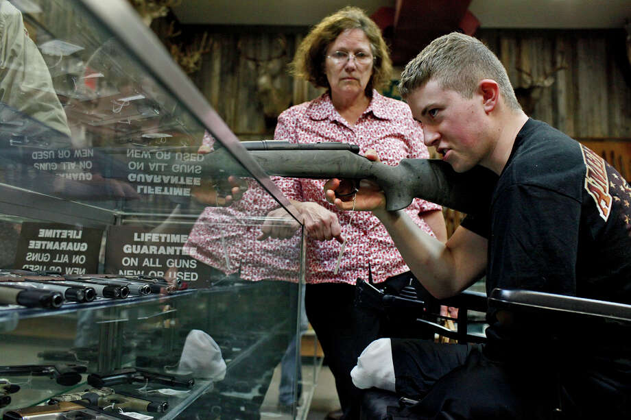 Saralee Trimble watches as her son, Army Pfc. Kevin Trimble, 19, shops for a hunting rifle at Dury's Gun Shop in San Antonio on Wednesday, March 7, 2012. Trimble was looking to buy his own rifle, since he's been borrowing one, for hunting trips with wounded warriors. Photo: Lisa Krantz, San Antonio Express-News / @San Antonio Express-News