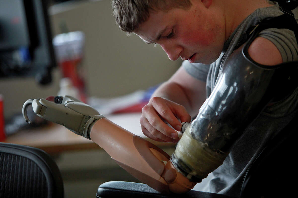 Army Pfc. Kevin Trimble, 19, adjusts his myoelectric upper limb prosthetic for occupational therapy at the Center for the Intrepid at Brooke Army Medical Center in San Antonio on Wednesday, March 7, 2012.