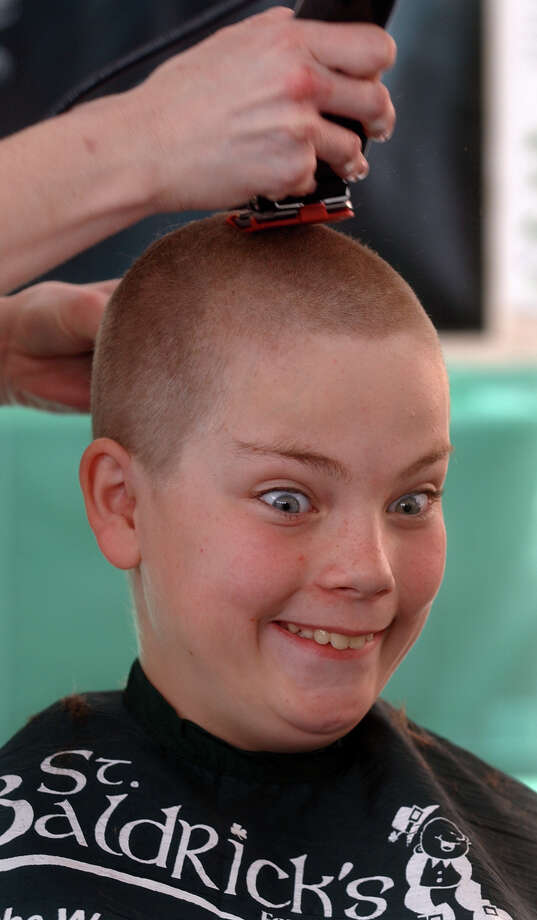 Thomas McCarthy, 11, reacts as his hair is shaved off, during a St. Baldrick's Foundation fundraiser to fight childhood cancer at Baker Pediatrics on Park Avenue in Trumbull, Conn. on Saturday April 14, 2012. McCarthy and five of his fellow teammates from the little league team, the CT Hitmen, and the coach Chris Carrafello, came out to get their heads shaved for the event. The CT Hitmen raised over $1200 towards cancer research. Photo: Christian Abraham / Connecticut Post
