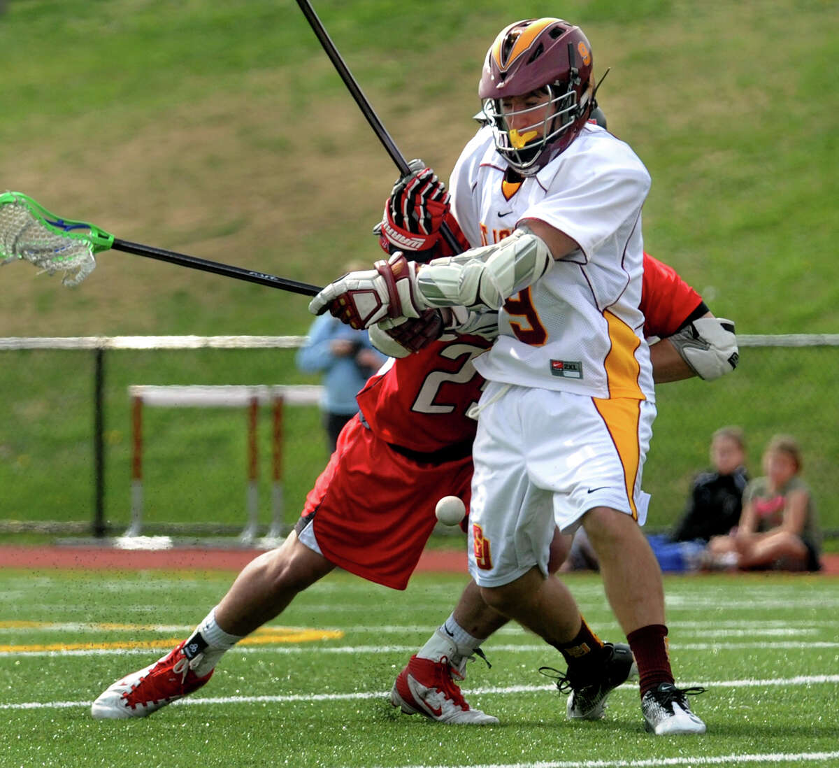 St. Joe's Christian Keator looses the ball as he is shoved from behind by New Canaan's #23 Griffin White, during boys lacrosse action in Trumbull, Conn. on Saturday April 14, 2012.
