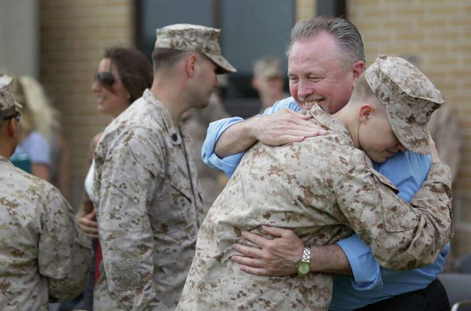 "Smith's father, Jerry, hugs Lance Cpl. Evan Mason after a ceremony at Ellington Field in Houston. The Smith family accepted a Bronze Star Medal with a combat ""V"" for valor awarded posthumously to their son. Photo: Melissa Phillip / © 2012 Houston Chronicle"