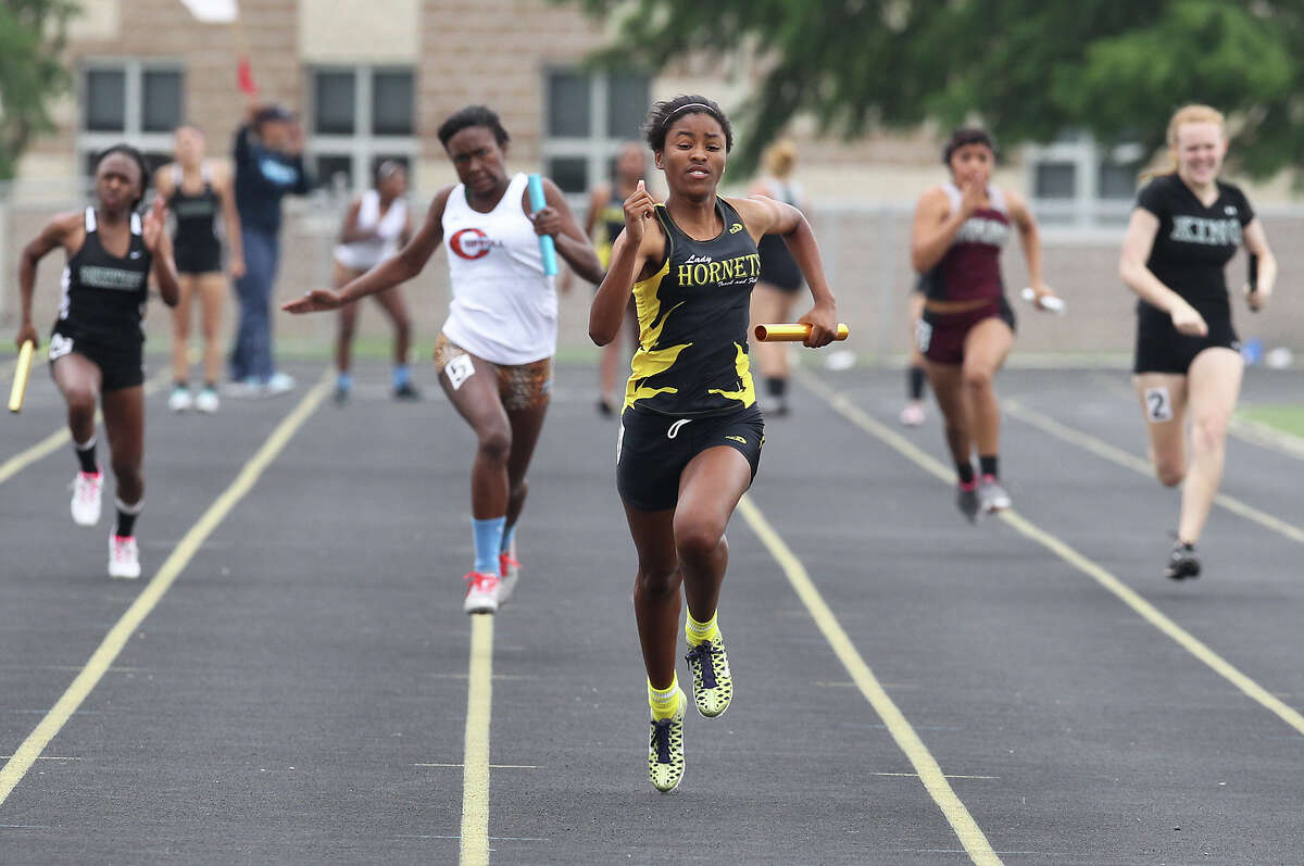 East Central's Raven Smith (center) anchors the last leg and helps earn first place for her team in the 400-meter relays at the District 28-5A track meet at East Central High School on Friday, Apr. 13, 2012. Kin Man Hui/Express-News.