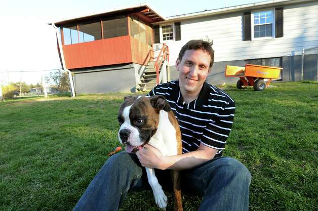 Mark Patterson sits with his boxer, Porter, in his backyard on Friday, April 6, 2012, in Selkirk, N.Y. (Cindy Schultz / Times Union) Photo: Cindy Schultz / 00017119A