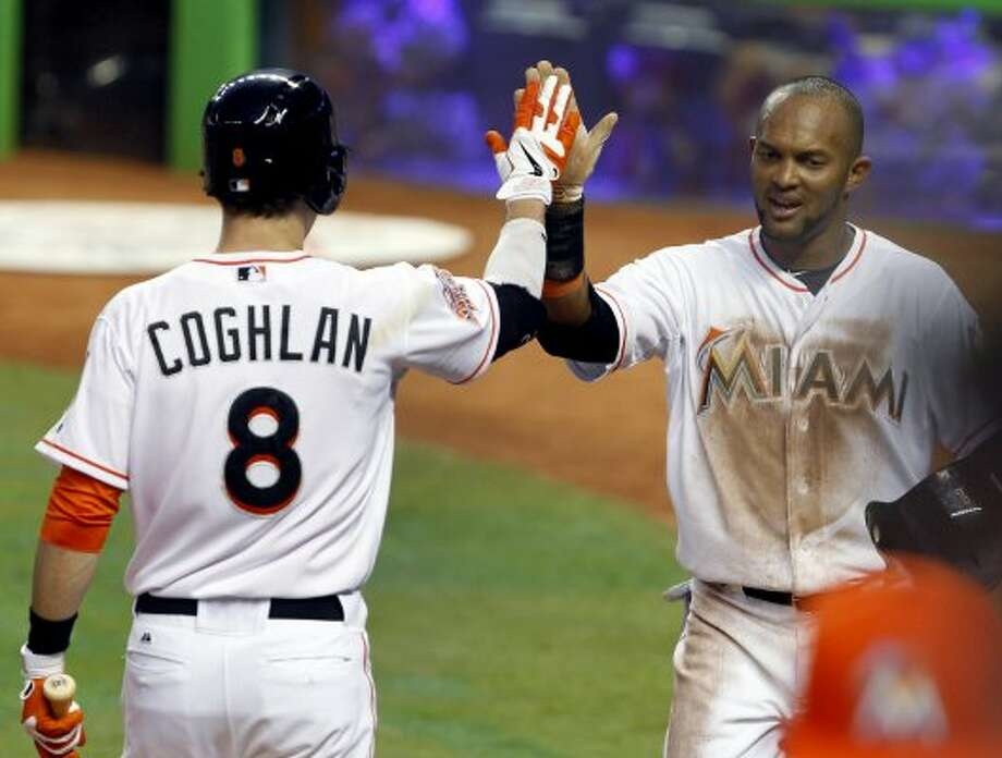 Miami's Emilio Bonifacio, right, is congratulated by Chris Coghlan (8) after scoring on a single by Logan Morrison during the first inning. (Wilfredo Lee / Associated Press)