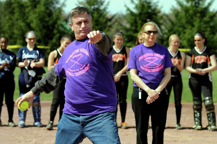 Frank Massa of Clifton Park, left, throws the ceremonial first pitch during the Christina Massa Memorial Softball Tournament on Saturday, April 14, 2012, at Clifton Park Commons in Clifton Park, N.Y. At right is his wife, Debbie. Their daughter, Christina, was a star Shenendehowa player who died in a car accident in May 2002 at the age of 18. The event raises money for scholarships given to current Shen athletes. (Cindy Schultz / Times Union) Photo: Cindy Schultz / 00017232A