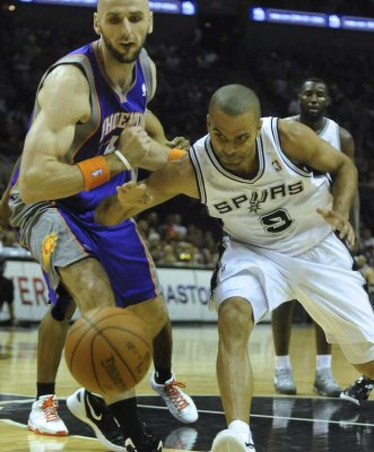 Tony Parker of the San Antonio Spurs (9) runs after a loose ball as Marcin Gortat of the Phoenix Suns watches during NBA action at the AT&T Center on Saturday, April 14, 2012. Billy Calzada / San Antonio Express-News (San Antonio Express-News)