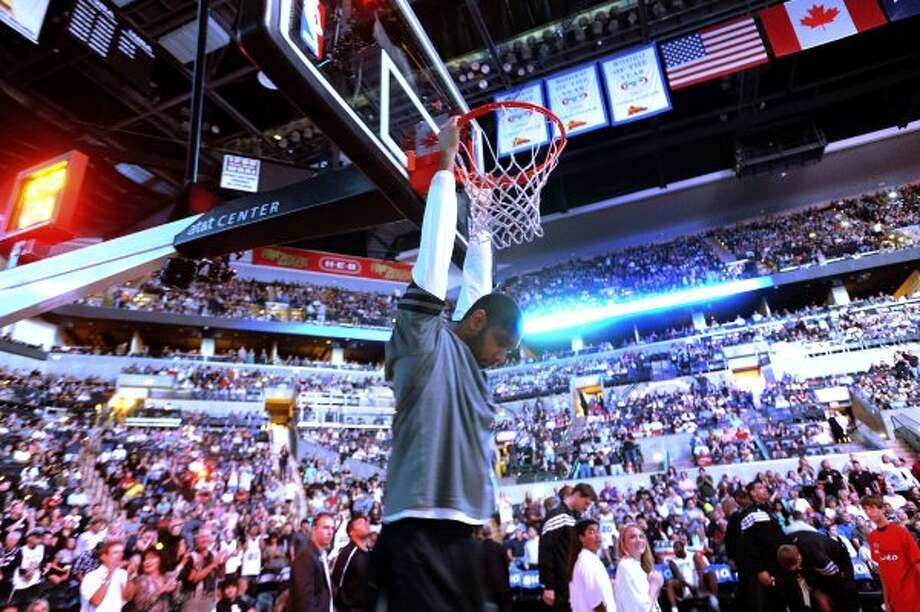 Tim Duncan of the San Antonio Spurs hangs from the rim before he and his teammates are introduced before their game against the Phoenix Suns at the AT&T Center on Saturday, April 14, 2012. Billy Calzada / San Antonio Express-News (San Antonio Express-News)