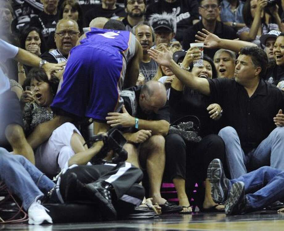 Ronnie Price of the Phoenix Suns runs into fans and a photographer during NBA action at the AT&T Center on Saturday, April 14, 2012. No one was hurt in the incident. Billy Calzada / San Antonio Express-News (San Antonio Express-News)