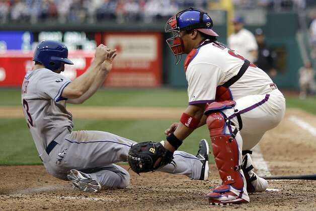 New York Mets' Mike Baxter, left, scores on a hit by Ruben Tejada as Philadelphia Phillies catcher Carlos Ruiz waits for the throw in the ninth inning of a baseball game on Saturday, April 14, 2012, in Philadelphia. New York won 5-0. (AP Photo/Matt Slocum) Photo: Matt Slocum, Associated Press