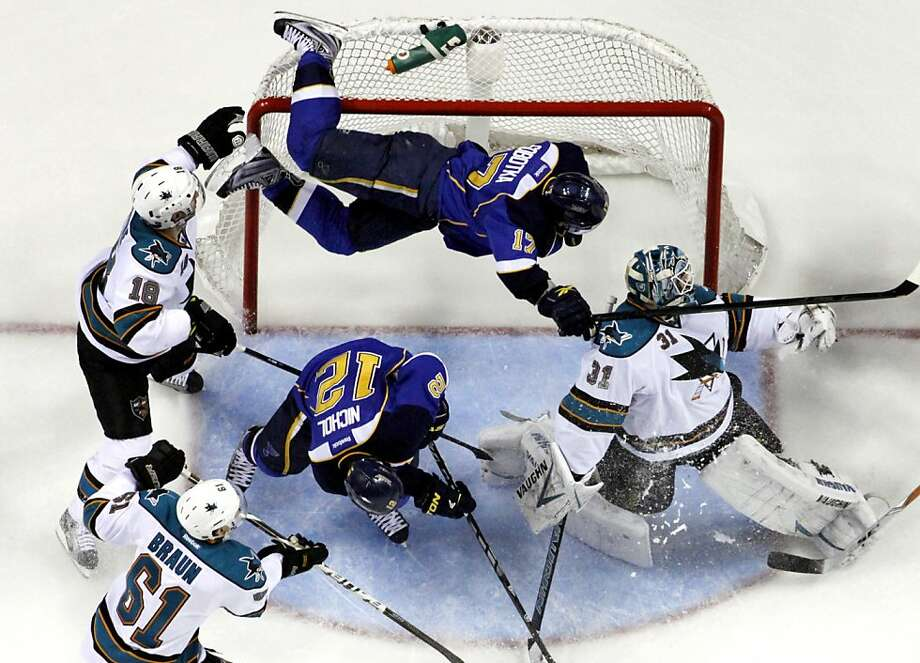 St. Louis Blues' Vladimir Sobotka, top, of the Czech Republic, goes flying into the goal over San Jose Sharks goalie Antti Niemi, right, of Finland, and Blues' Scott Nichol (12) as Sharks' Dominic Moore (18) and Justin Braun (61) watch during the second period in Game 2 of an NHL Stanley Cup first-round hockey playoff series Saturday, April 14, 2012, in St. Louis. (AP Photo/Jeff Roberson) Photo: Jeff Roberson, Associated Press