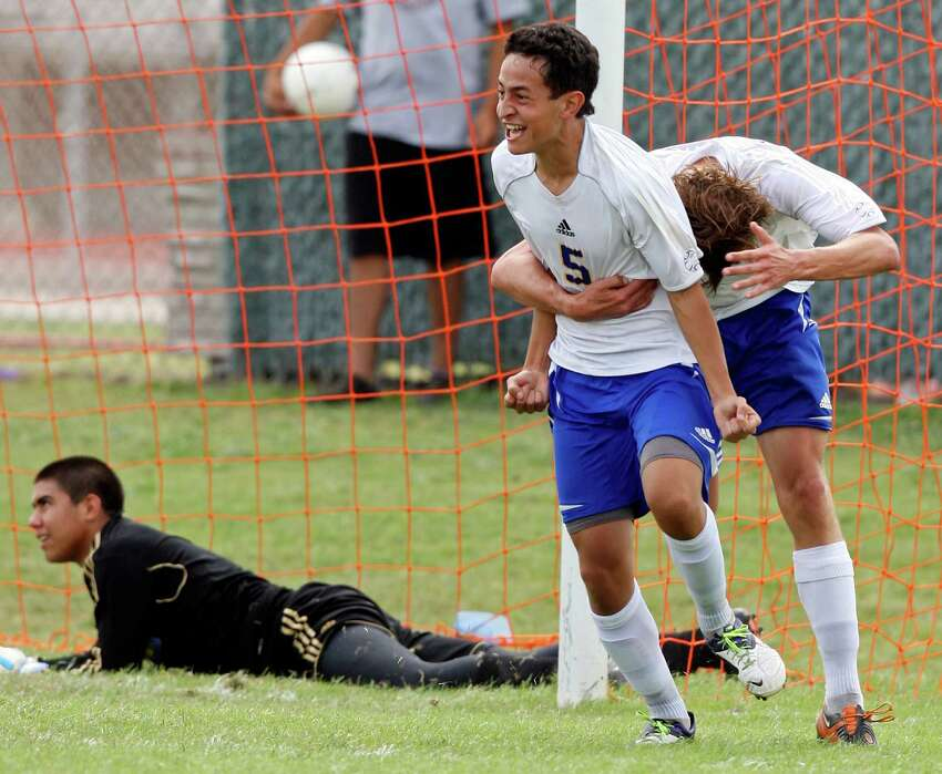 Alamo Heights' Jesus Espin (left) celebrates with teammate Alamo Heights' Matthew Struble after scoring a goal against Pharr Valley View's Javier Olvera (background) during second half action of their Region IV-4A final held April 14, 2012 at Cabaniss Field in Corpus Christi, Tx. Alamo Heights won 4-1.