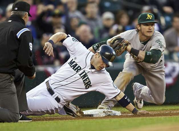 Brendan Ryan #26 of the Seattle Mariners slides safely into third base ahead of the tag of Josh Donaldson #20 of the Oakland Athletics during a game at Safeco Field on April 14, 2012 in Seattle, Washington. Photo: Stephen Brashear, Getty Images
