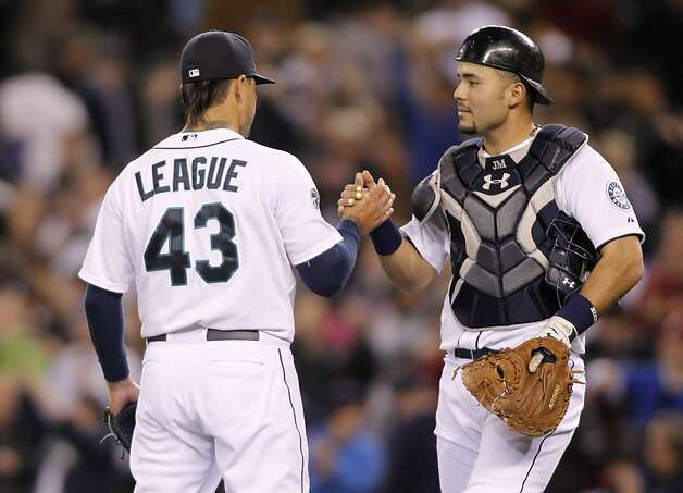Seattle Mariners catcher Jesus Montero congratulates closing pitchers Brandon League after the 4-0 win over the Oakland Athletics of a baseball game in Seattle Saturday, April 14, 2012. Photo: John Froschauer, Associated Press