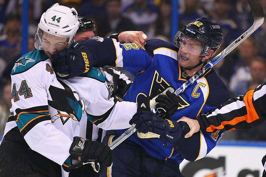 David Backes #42 of the St. Louis Blues tussles with Marc-Edouard Vlasic #44 of the San Jose Sharks