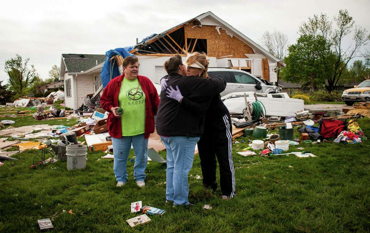 CRESTON, IA - APRIL 15: Neighbors and friends embrace while surveying the damage left behind by tornado April 15, 2012 in Creston, Iowa. Parts of the northern edge of Creston were affected by strong winds and tornados including damage to the Greater Regional Medical Center. The storms were part of a massive system that affected areas from Northern Nebraska and Iowa south through Oklahoma. (Photo by Eric Francis/Getty Images)