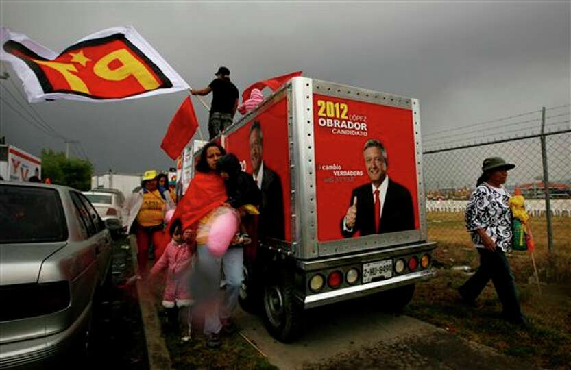 People walk past a truck covered in pictures of Manuel Lopez Obrador, presidential candidate for the