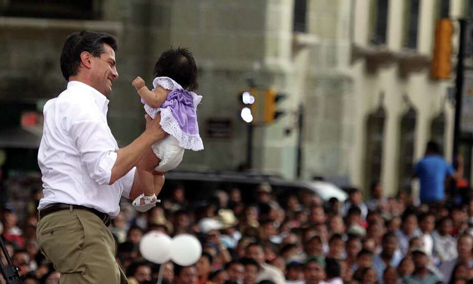 Mexican presidential candidate for the Institutional Revolutionary Party (PRI), Enrique Pena Nieto, holds a baby during a rally in Oaxaca de Juarez, Oaxaca State, Mexico on April 11, 2012. Mexico will hold presidential elections next July 1, 2012. AFP PHOTO/ Carlos SALINAS Photo: CARLOS SALINAS, Getty Images / 2012 AFP