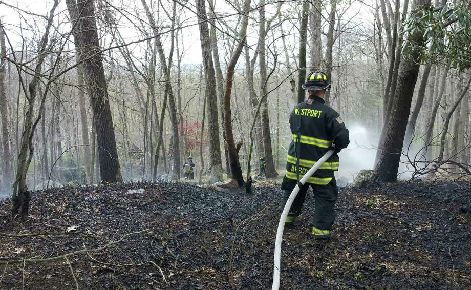 Westport firefighters extinguished a brush fire in the area of Butternut and Greenbrier lanes Sunday afternoon. No injuries or significant damage were reported. Photo: Westport Fire Department / Westport News contributed