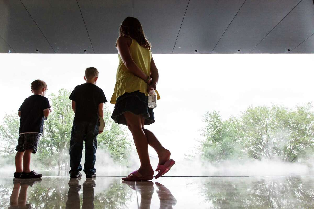 Jack Thibaut, 6, (left to right), his brother Judah, 6, and sister Isabella, 7, look at the reflecting pool at the Asia Society Texas Center during the
